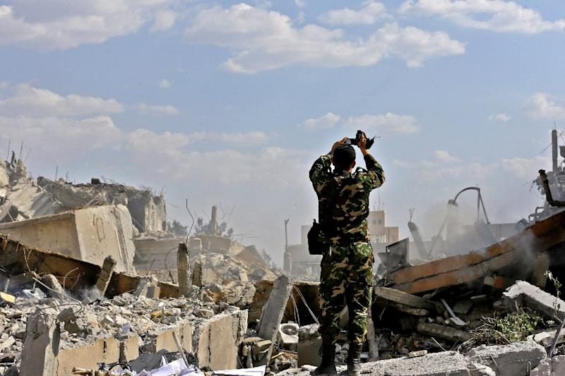 A Syrian soldier inspects the wreckage of a building described as part of the Scientific Studies and Research Centre (SSRC) compound in the Barzeh district north of Damascus, during a press tour organised by the Syrian government after US-led strikes (AFP Photo/LOUAI BESHARA)