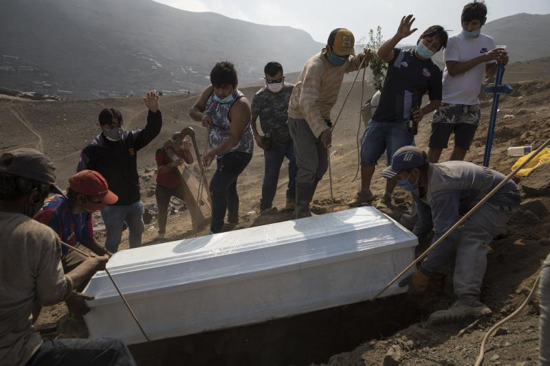 Relatives bury their 85-year-old grandfather Lupicino Fernandez who died of the new coronavirus, at the Nueva Esperanza cemetery on the outskirts of Lima, Peru, Wednesday, May 27, 2020. (AP Photo/Rodrigo Abd)