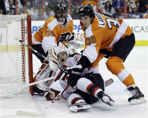 New Jersey Devils' David Clarkson, center, is knocked to the ice by Philadelphia Flyers' Oliver Lauridsen, right, as Ilya Bryzgalov, of Russia, watches during the first period of an NHL hockey game, Thursday, April 18, 2013, in Philadelphia. (AP Photo/Matt Slocum)