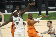 Phoenix Suns guard Chris Paul, center, fights for a rebound with Milwaukee Bucks guard Jrue Holiday (21) and center Brook Lopez, right, during the first half of Game 4 of basketball's NBA Finals in Milwaukee, Wednesday, July 14, 2021. (AP Photo/Paul Sancya)