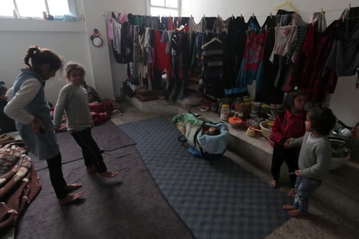 Internally displaced children stand near hanging clothes inside a room in Azaz