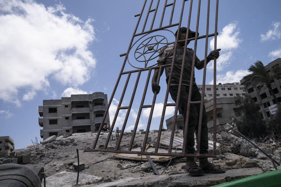 People gather reclaimable debris from the site of a building previously destroyed by an air-strike after an 11-day war between Gaza's Hamas rulers and Israel, in Gaza City, Saturday, May 22, 2021. (AP Photo/John Minchillo)