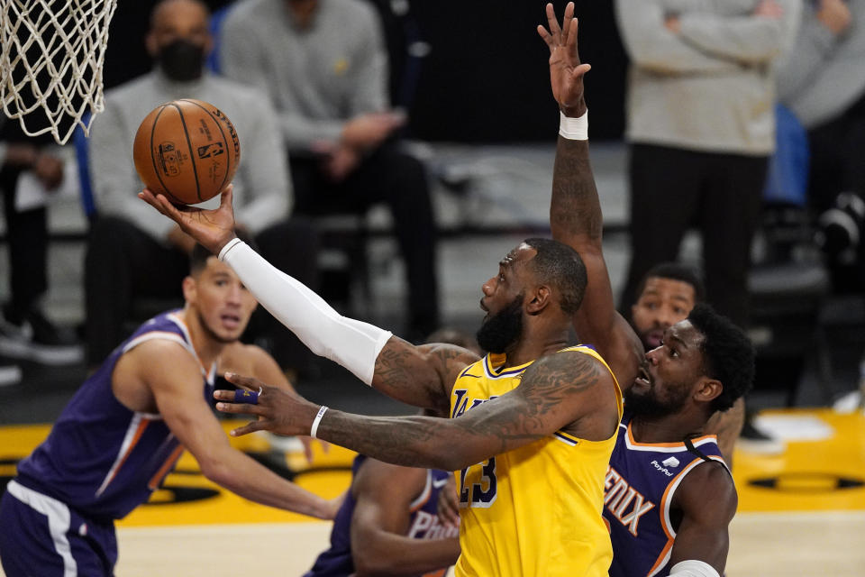 Los Angeles Lakers forward LeBron James, left, shoots as Phoenix Suns center Deandre Ayton defends during the second half of an NBA basketball game Tuesday, March 2, 2021, in Los Angeles. (AP Photo/Mark J. Terrill)