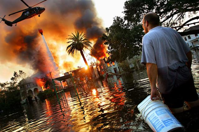 A helicopter tries to extinguish a fire in New Orleans after Hurricane Katrina. Because of the extensive flooding caused by the breaking of the city's levies, fire trucks were unable to reach burning homes, and in some cases whole blocks burned to the ground. (Photo: Craig Warga/NY Daily News Archive via Getty Images)