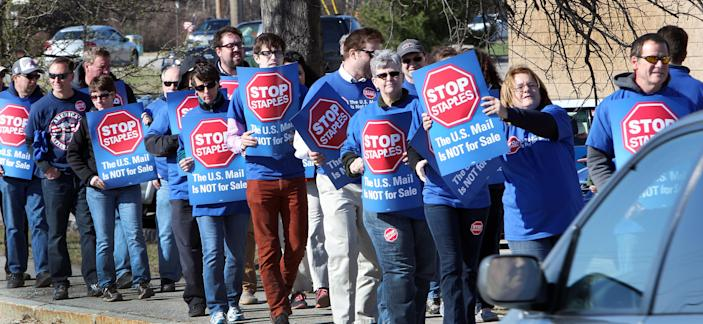 Postal workers picket in front of a Staples store Thursday April 24, 2014 in Concord, N.H. Postal workers around the country protested in front of Staples stores, objecting to the U.S. Postal Service's pilot program to open counters in stores, staffed with retail employees. (AP Photo/Jim Cole)