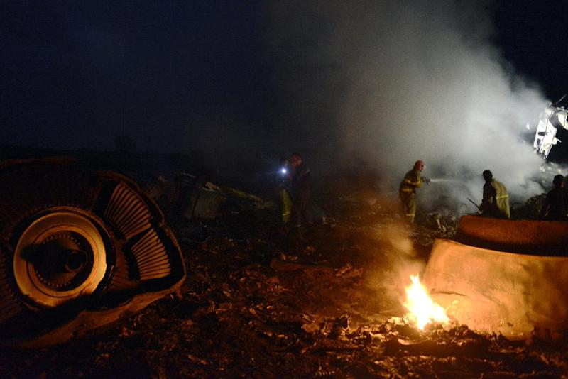 Firefighters extinguish a fire amongst the wreckage of flight MH17 on July 17, 2014 (AFP Photo/Alexander Khudoteply)