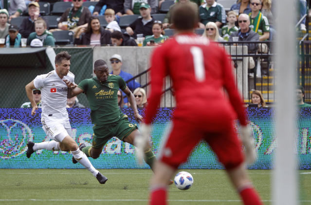 Portland Timbers' Fanendo Adi, center, dribbles past an LAFC defender as LAFC goalkeeper Tyler Miller (1) guards the net during an MLS soccer game, Saturday, May 19, 2018, in in Portland, Ore. (Sean Meagher//The Oregonian via AP)