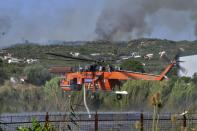 An helicopter fills water during a wildfire near Pyrgos town, western Greece, Thursday, Aug. 5, 2021. Wildfires rekindled outside Athens and forced more evacuations around southern Greece Thursday as weather conditions worsened and firefighters in a round-the-clock battle stopped the flames just outside the birthplace of the ancient Olympics. (Giannis Spyrounis/ilialive.gr via AP)
