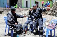Artisanal gold miners drink beer on a street in La Rinconada, in the Andes