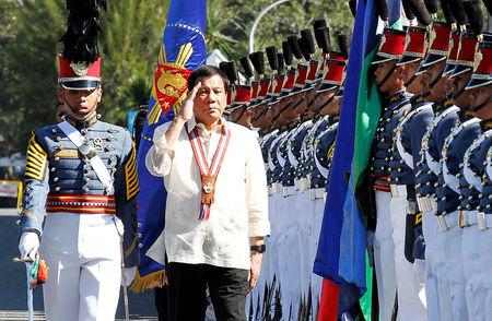 Philippine President Rodrigo Duterte salutes during arrival honours at the Philippine Military Academy in Baguio city, in northern Philippines March 12, 2017.    REUTERS/Harley Palangchao
