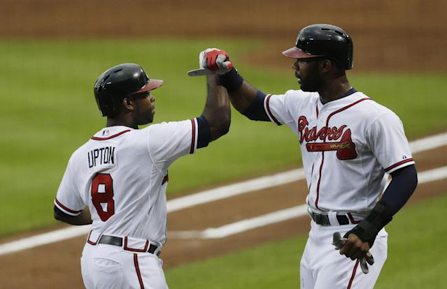Atlanta Braves left fielder Justin Upton (8) celebrates with teammate Jason Heyward after hitting a two-run home run in the first inning of a baseball game against the Colorado Rockies in Atlanta, Thursday, Aug. 1, 2013. (AP Photo/John Bazemore)