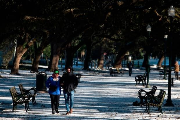 A couple walks in Hermann Park covered in snow in Houston on Monday.