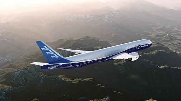 A Boeing 777 flying over mountainous terrain
