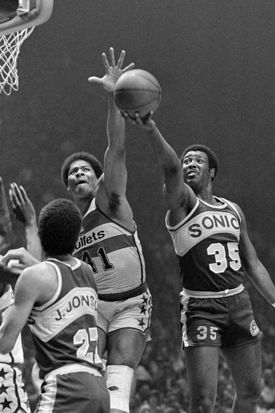 FILE - In this May 25, 1979, file photo, Washington Bullets' Wes Unseld (41) reaches to block a shot by Seattle Supersonics' Paul Silas ()35) during an NBA basketball game in Landover, Md. Unseld, the Hall of Fame center who led Washington to its only NBA championship and was chosen one of the 50 greatest players in league history, died Tuesday, June 2, 2020, after a series of health issues, most recently pneumonia. He was 74. (AP Photo/Smith, File)