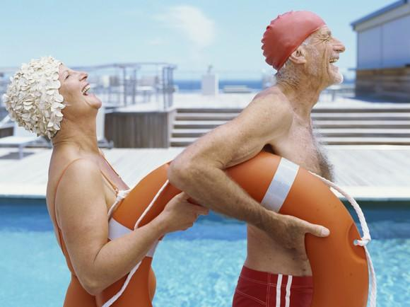Two seniors laugh while carrying a life preserver.