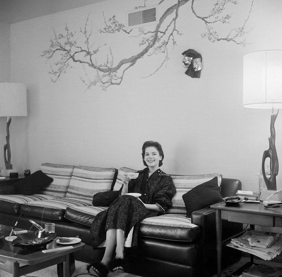 <p>Natalie Wood smiles as she enjoys a cup of tea from the couch of her Los Angeles living room in 1957. </p>