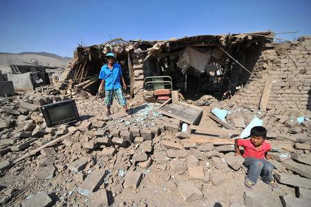 A man and a child stand at debris of a building after a strong magnitude 7.1 earthquake struck the coast of southern Peru, in Acari, Arequipa , Peru, January 14, 2018. REUTERS/Diego Ramos