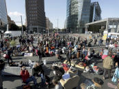 Supporters of the 'Extinction Rebellion' movement block a road at the Potsdamer Platz square in Berlin, Germany, Monday, Oct. 7, 2019. The activists want to draw attention on the climate protest by blocking roads and with other acts of civil disobedience in Berlin and other cities around the world. (AP Photo/Michael Sohn)