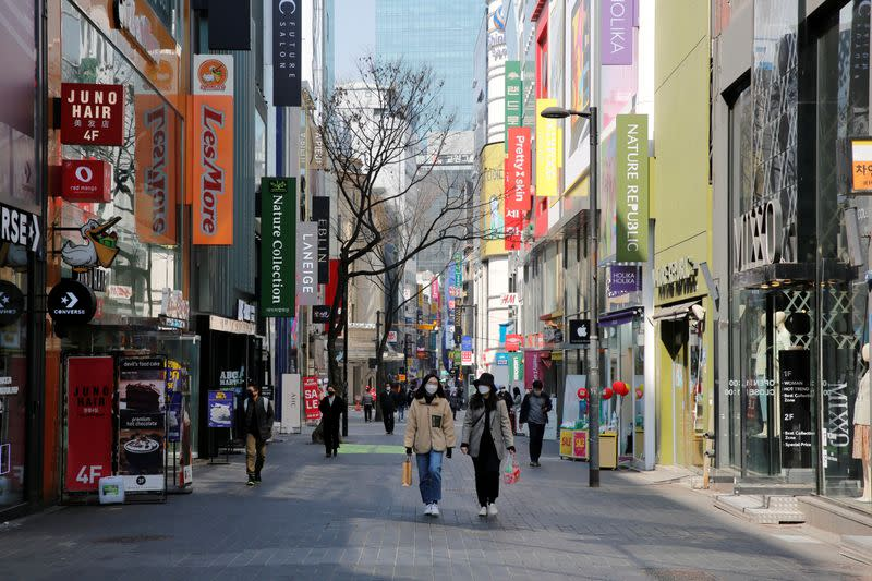 Women, wearing masks to prevent contracting coronavirus, walk in shopping district in Seoul