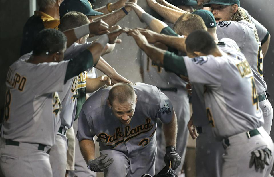 Oakland Athletics' Brandon Moss celebrates with teammates after hitting a two-run home run against the Detroit Tigers in the fifth inning of a baseball game in Detroit, Tuesday, Aug. 27, 2013. (AP Photo/Paul Sancya)