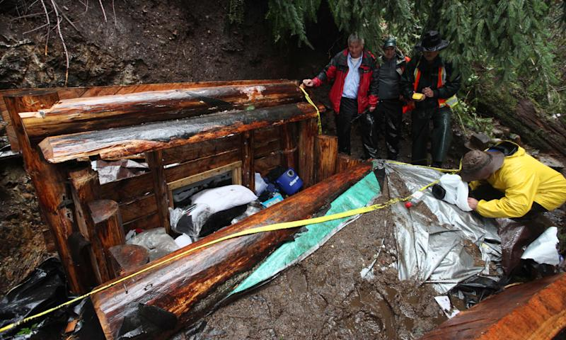 Journalists and officials peer into the top of a multi-level bunker dug into the side of a remote ridge where murder suspect Peter Keller died days earlier, Monday, April 30, 2012, near North Bend, Wash. Keller spent eight years carving his hole in the side of the mountain, camouflaging the rugged underground bunker with ferns and sticks and stocking it with a generator and ammunition boxes sealed in Ziploc bags. Suspected in the deaths of his wife, daughter and pets last weekend, he headed there prepared for the long haul with high-powered rifles, scope and body armor. Police pumped in tear gas, called for him over bullhorns, and, after 22 hours, set off explosives along the top of the bunker Saturday. He was found dead of a self-inflicted gun shot. (AP Photo/Elaine Thompson)