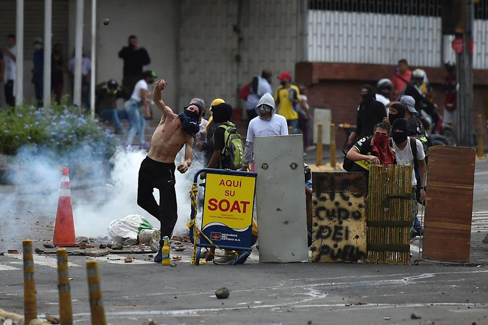 A demonstrator throws a rock to riot police officers during a protest against the government in Cali, Colombia, on May 10, 2021. - Faced with angry street protests and international criticism over his security forces' response, Colombia President Ivan Duque is coming across as erratic and out of touch with a country in crisis, analysts say. Since April 28, hundreds of thousands of people have vented their frustrations against the government after poverty and violence soared during the pandemic. (Photo by Luis ROBAYO / AFP) (Photo by LUIS ROBAYO/AFP via Getty Images)