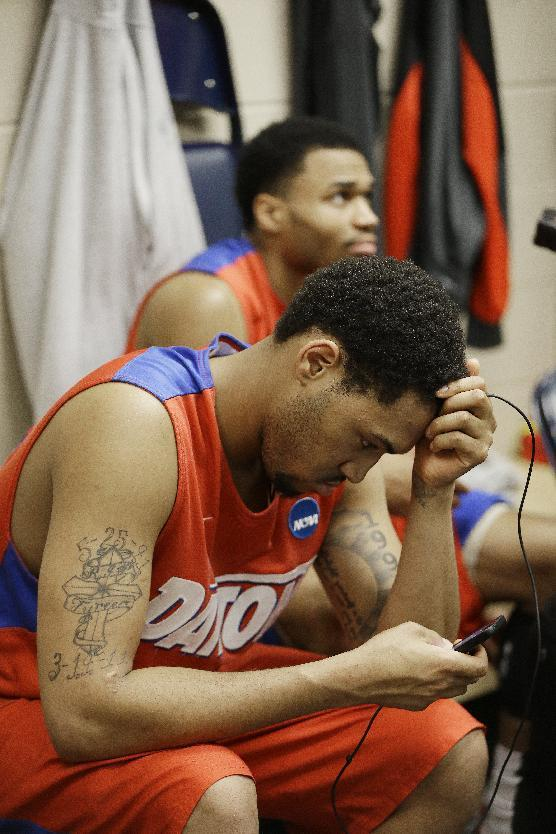 Dayton's Jalen Robinson, foreground and Vee Sanford sit in the locker room after the second half in a regional final game against Florida at the NCAA college basketball tournament, Saturday, March 29, 2014, in Memphis, Tenn. Florida won 62-52. (AP Photo/Mark Humphrey)