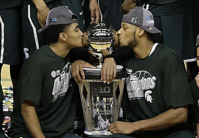 Michigan State's Gary Harris, left, and Adreian Payne kiss the championship trophy after they defeated Michigan 69-55 in an NCAA college basketball game in the championship of the Big Ten Conference tournament on Sunday, March 16, 2014, in Indianapolis. (AP Photo/AJ Mast)