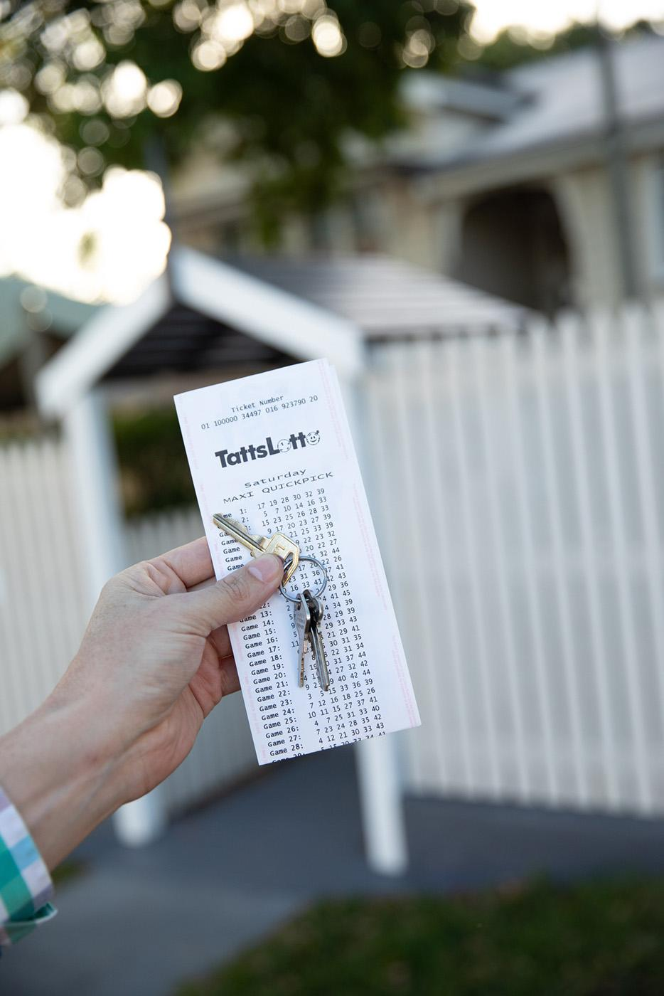 A hand holds a set of house keys and a TattsLotto ticket in front of a white picket fence.