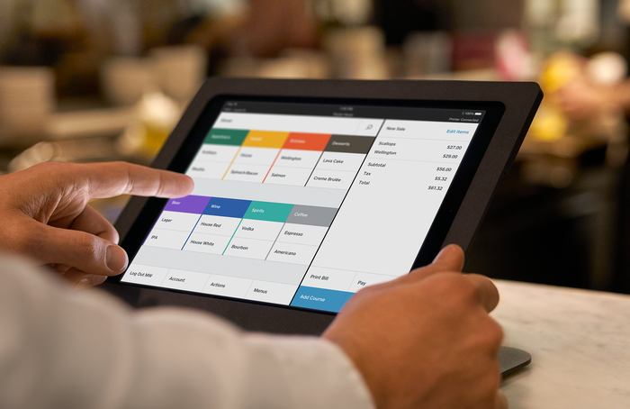 A person holding a tablet displaying the Square for Restaurants platform.