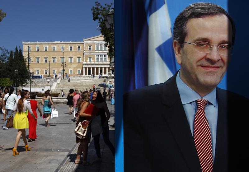 People walk in Syntagma square next to a New Democracy elections kiosk bearing a poster of Greek conservative leader Antonis Samaras in Athens, Tuesday, June 12, 2012. Greece faces crucial national elections on Sunday, that could ultimately determine whether the debt-saddled, recession bound country remains in the eurozone. First elections on May 6 resulted in a hung parliament. (AP Photo/Petros Karadjias)