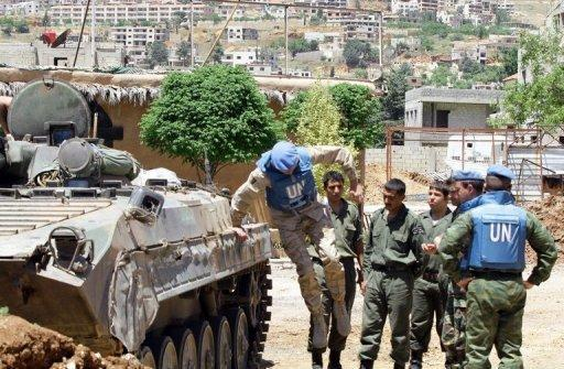 A UN monitor jumps off a tank during a visit to a military outpost at the entrance of the Syrian city of Zabadani