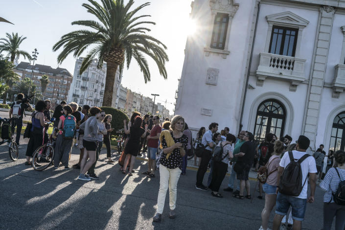 <p>People await in a local square the arrival of refugees at the port of Valencia. (Photo: José Colón for Yahoo News) </p>