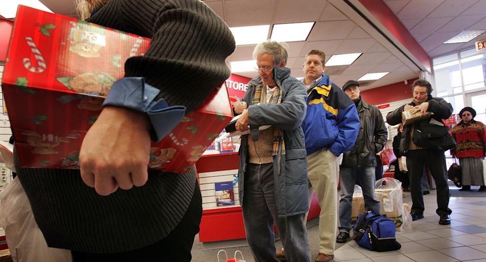 People lined up at a post office mailing Christmas presents