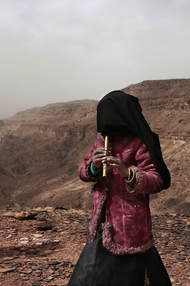 In this March 30, 2019 photo, Aicha, an Egyptian Bedouin from the Hamada tribe and one of the first female guides, plays the flute for tourists on a trek in the mountains, near Wadi Sahw, Abu Zenima, in South Sinai, Egypt. Four Bedouin women are for the first time leading tours in Egypt's Sinai Peninsula, breaking new ground in their deeply conservative community, where women almost never work outside the home or interact with outsiders. (AP Photo/Nariman El-Mofty)