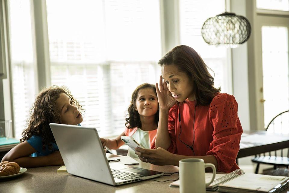 A woman tries to work on her computer while two young girls try to get her attention.