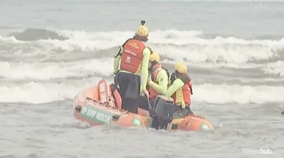 Rescuers search New Zealand's Kiritehere Beach for the missing Phillips family.