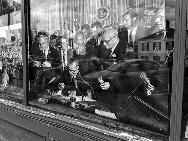 <p>A 1965 photo of Martin Luther King Jr and other leaders behind President Lyndon B. Johnson as he signed the 1965 Voting Rights Act is displayed behind a shattered window in downtown Selma, Ala. (Photo: Holly Bailey/Yahoo News) </p>