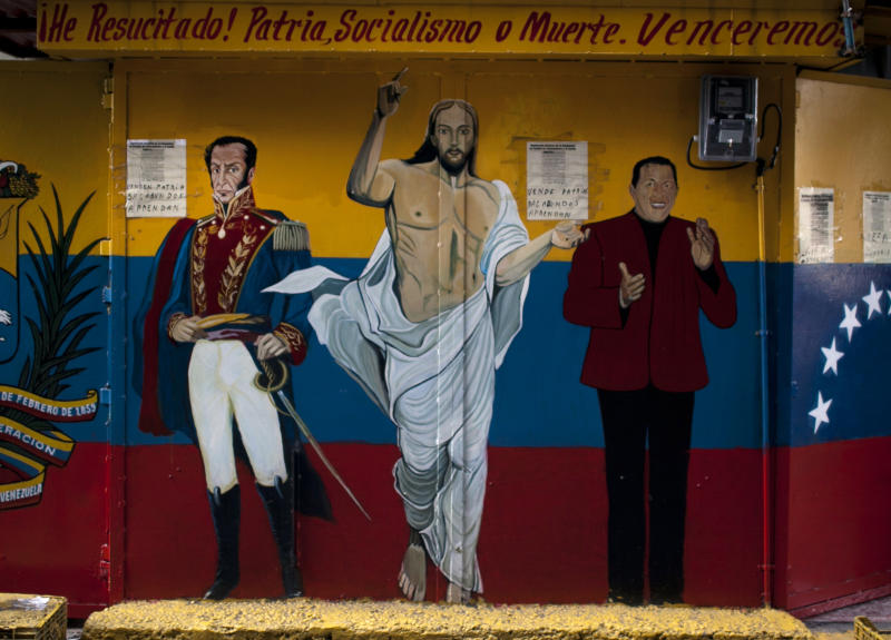 "A mural of Venezuela's independence hero Simon Bolivar, left, Jesus, center, and Venezuela's President Hugo Chavez reads in Spanish ""I have risen! Homeland, Socialism or Death. We will overcome"" in Caracas, Venezuela, Tuesday Feb. 28, 2012. Doctors successfully extracted a tumor from Chavez's pelvic region and he was stable and recovering in Cuba on Tuesday with family at his side, his vice president announced. (AP Photo/Ariana Cubillos)"