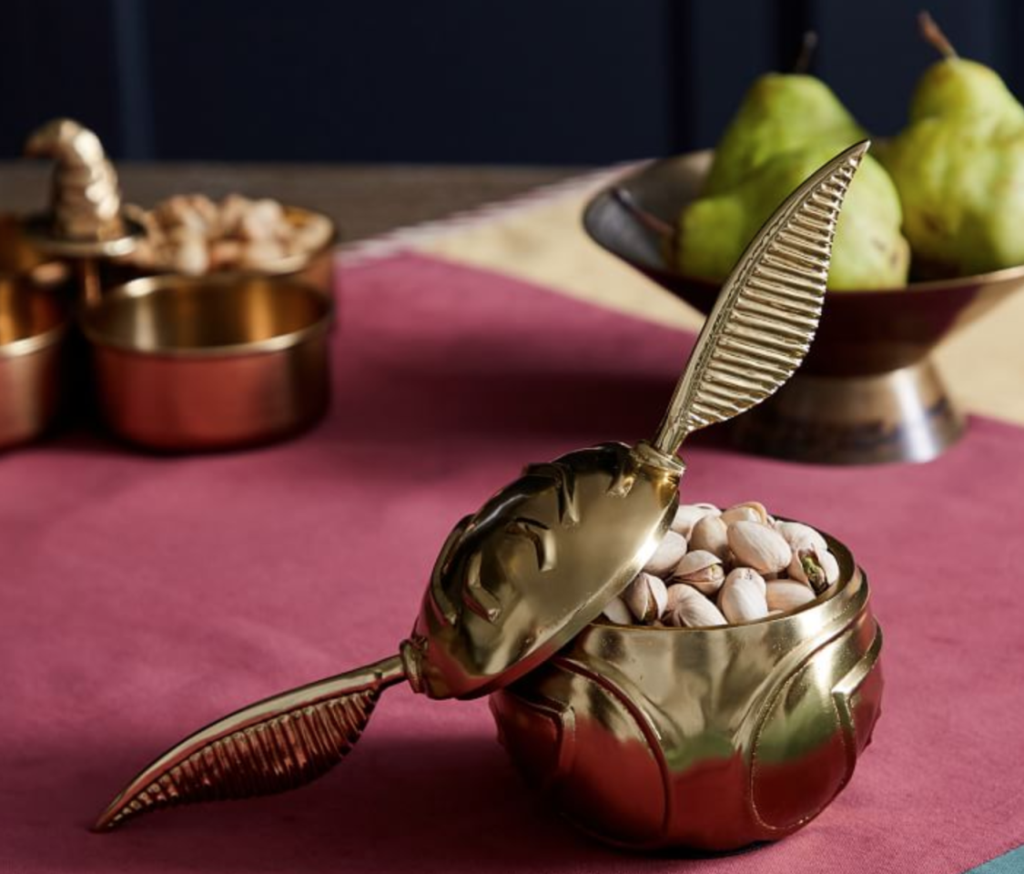 """<p>The ultimate Potter centerpiece, but even better because it holds snacks.</p> <p><strong>Harry Potter Golden Snitch Snack Bowl, $40 at <a href=""""http://pottery-barn.7eer.net/c/249354/267848/4332?subId1=FW%2Csnitch-bowl-pottery-barn-harry-potter-gifts-1118.jpg%2Cmsoll1271%2C%2CIMA%2C1323733%2C201910%2CI,FW&u=https%3A%2F%2Fwww.potterybarn.com%2Fproducts%2Fharry-potter-tidbit-bowl%2F"""" target=""""_blank"""">potterybarn.com</a></strong></p>"""