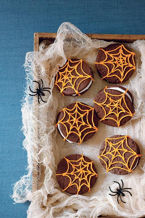 """<p>These sandwiches — made from soft chocolate cookies and cream cheese filling — are so cute, they can be wrapped up and given out to trick-or-treaters individually. </p><p><strong><em><a href=""""https://www.womansday.com/food-recipes/food-drinks/recipes/a11268/chocolate-spiderweb-sandwich-cookies-recipe-123438/"""" rel=""""nofollow noopener"""" target=""""_blank"""" data-ylk=""""slk:Get the Chocolate Spiderweb Sandwich Cookies recipe."""" class=""""link rapid-noclick-resp"""">Get the Chocolate Spiderweb Sandwich Cookies recipe. </a></em></strong></p>"""