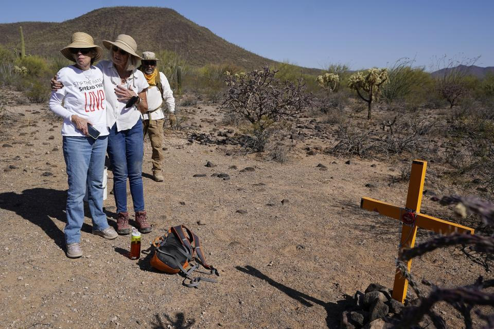 Tucson Samaritans volunteer Michele Maggiora, center, embraces Eileen O'Farrell Smith, left, as Peter Lucero, right, looks on at the site of a newly placed cross to identify a deceased migrant in the desert near Three Points, Ariz., on Tuesday, May 18, 2021. (AP Photo/Ross D. Franklin)