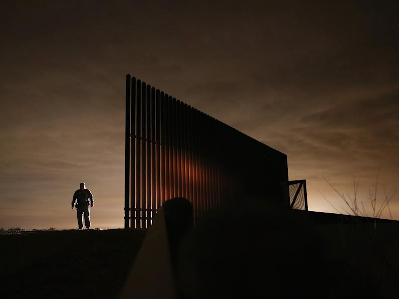 US Border Patrol agent Sal De Leon stands near a section of the US-Mexico border fence while stopping on patrol on in La Joya, Texas: Getty