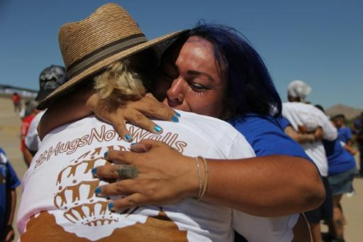 Members of a Mexican family separated by the US border embrace briefly along the frontier