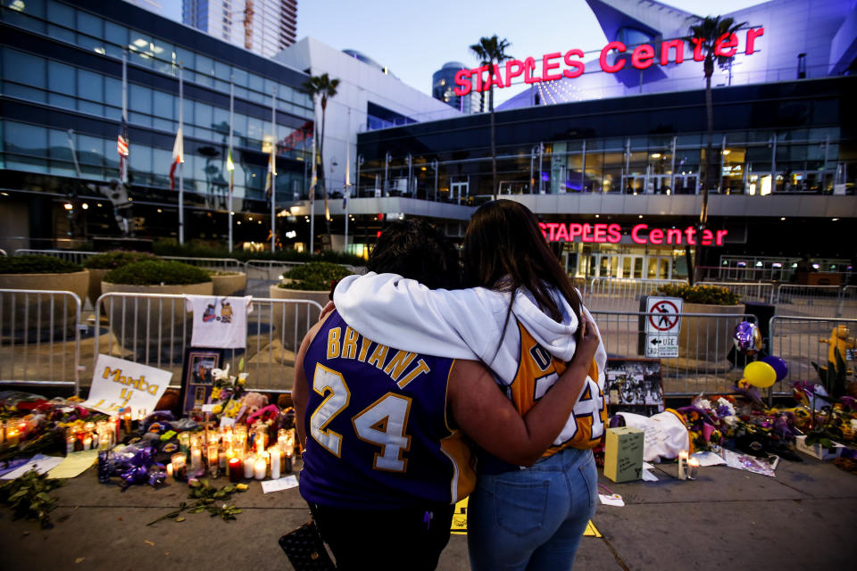 Fans pay their respects at a memorial for Kobe Bryant in front of Staples Center, Tuesday, Jan. 28, 2020, in Los Angeles. Bryant, the 18-time NBA All-Star who won five championships and became one of the greatest basketball players of his generation during a 20-year career with the Los Angeles Lakers, died in a helicopter crash Sunday. (AP Photo/Ringo H.W. Chiu)