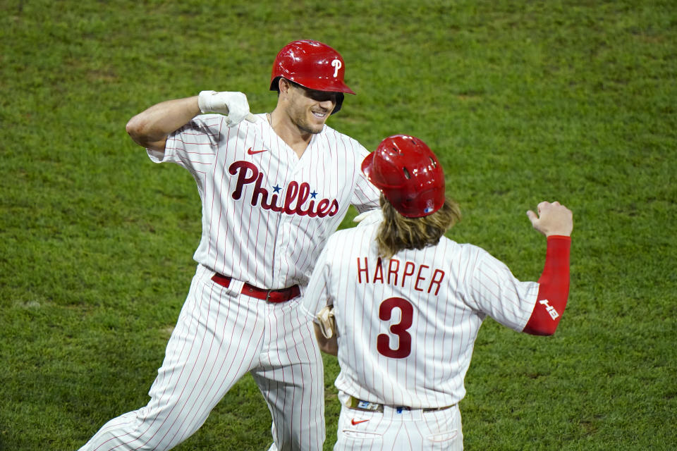 Philadelphia Phillies' J.T. Realmuto, left, and Bryce Harper celebrate after Realmuto's three-run home run off New York Mets pitcher Walker Lockett during the fifth inning of a baseball game, Friday, Aug. 14, 2020, in Philadelphia. (AP Photo/Matt Slocum)