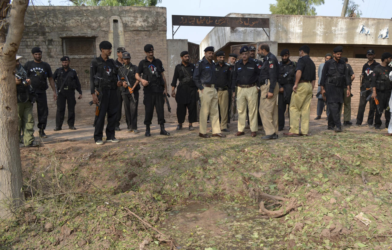Pakistani police officers gather at the site of a bombing in Peshawar, Pakistan, Monday, Oct. 7, 2013. The bomb exploded next to a van carrying security officials who were supposed to protect workers giving out anti-polio vaccinations on Monday, said Pakistani officials. (AP Photo/Mohammad Sajjad)