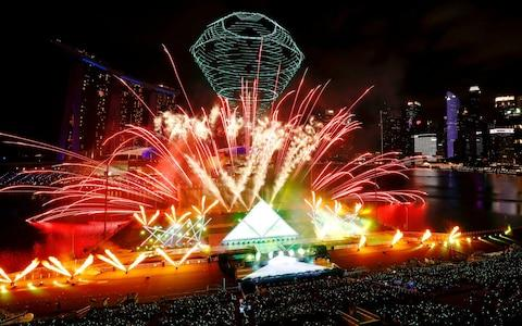 <span>Fireworks explode over Marina Bay during New Year's Eve celebrations in Singapore</span> <span>Credit: Reuters </span>
