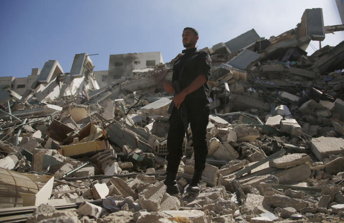 A policeman stands on rubble from a building housing AP office and other media in Gaza City that was destroyed after Israeli warplanes demolished it, Saturday, May 15, 2021. The airstrike Saturday came roughly an hour after the Israeli military ordered people to evacuate the building. There was no immediate explanation for why the building was targeted. (AP Photo/Hatem Moussa)