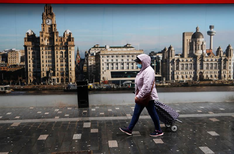A woman wearing a face mask walks on the street in Liverpool